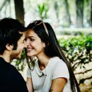Smiling couple sitting on park bench in city leaning in to kiss