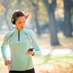 Young woman with headphones jogging in autumn nature and looking to mobile phone